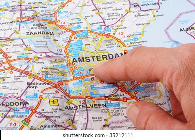 Close up of a hand pointing out Amsterdam on the map.