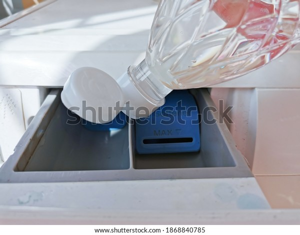 Close up hand pouring the vinegar into the front-loading drawer. Clean a washing machine with vinegar.