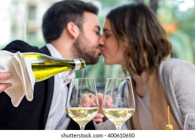 Close up of hand pouring white wine in glass with romantic out of focus couple in background.