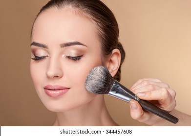 Close up of hand of professional make-up artist applying powder on female check. She is holding a brush. The woman closed eyes with pretty smile