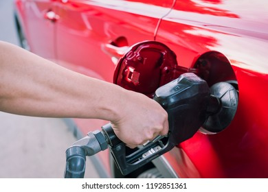 close up of a hand pumping gas into a car