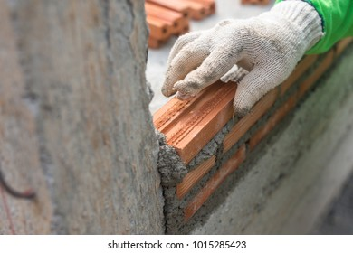 Close up Hand pushes down brick in cement building a wall on construction site