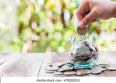 Close up hand putting coins in money jar. savings concept.