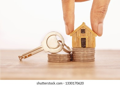 Close up hand putting house model place on stacking of money coin for home mortgage and loan ,  refinance or property investment concept