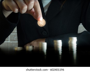 Close up hand putting money coins stack in saving money or growing business concept