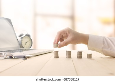 Close up Hand putting money coins stack for saving money or investment and growing business concept