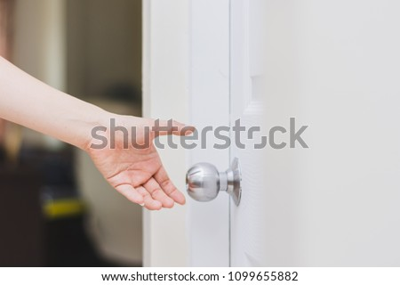 Close Up Of Womanu0027s Hand Reaching To Door Knob, Opening The Door