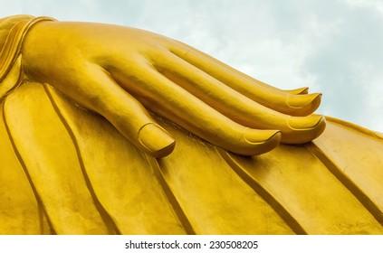 Close up of a hand reclining golden Buddha