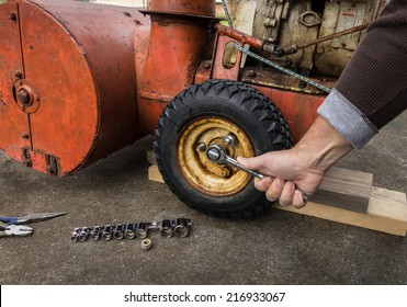 Close up of a hand removing snow blower bolts to replace a tire