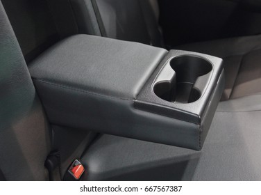 The close up of hand rest with cup holders, back car seat.