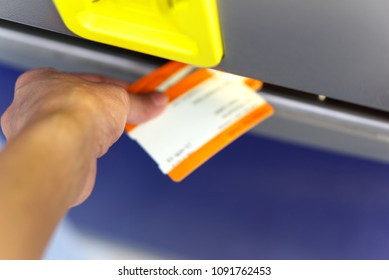 Close up of a hand retrieving travel tickets from a rail ticket dispensing machine