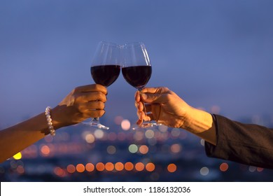 close up hand of romantic couple or friendship which happy moment relaxing ,red,wineglass,celebration on the rooftop in the night with bokeh background
