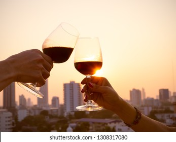 close up hand of romantic couple or friendship which happy moment relaxing ,red,wineglass,celebration on the rooftop with sunset sky scene