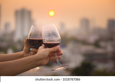 close up hand of romantic couple or women friendship which happy moment relaxing ,red,wineglass,celebration on the rooftop with sunset sky scene