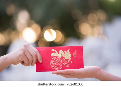 Close up hand sending and receiving red envelope Symbols of the Chinese New Year on golden bokeh background. gifts, festivals and celebration concept