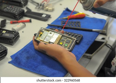 Close up hand spay spray cleaning circuit boards of electronic.