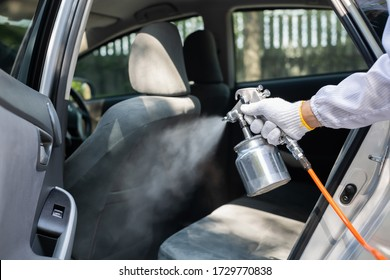 Close up hand of specialist cleaner wearing personal protective equipment PPE using chemical alcohol spray cleaning inside car to disinfect and decontaminate coronavirus covid-19