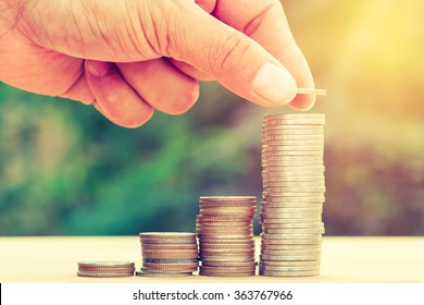 Close up of hand stacking gold coins with green bokeh background ,Business Finance and Money concept,Save money for prepare in the future.