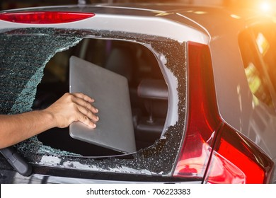 Close up hand stealing laptop from back side of car which rear glass broken.