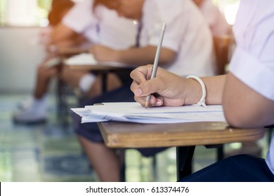 Close up hand of student reading and writing exam with stress.