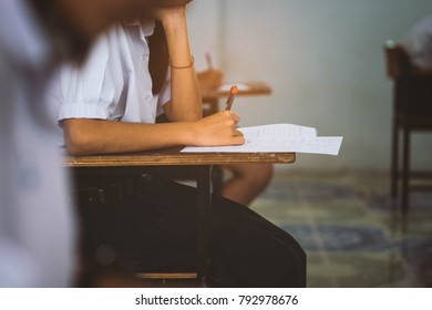 Close up hand of student reading and writing exam with stress in classroom.