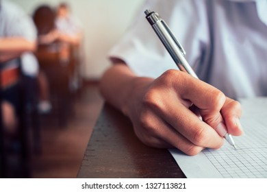Close up to hand of student is taking exam and writing answer in classroom for education test concept