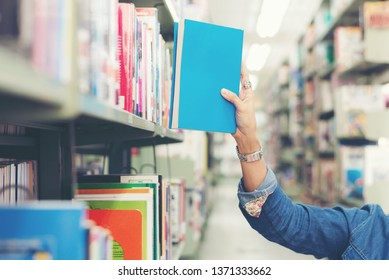 Close up hand student women finding book for reading in library.  Education  Concept