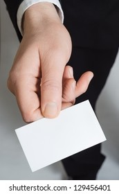 Close up of the hand of a suited business man, reaching forward to present a blank business card face upwards to the viewer.