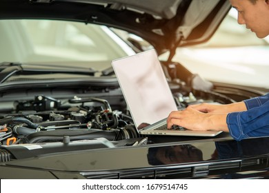 Close up hand Technician use computer Analyze car problems and repairs the car in the garage,Mechanic check car concept.