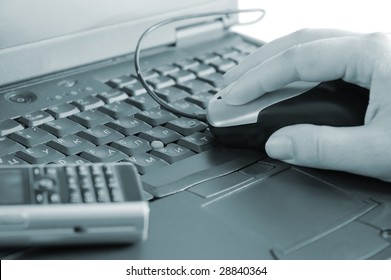 Close up of a hand and telephone on laptop keyboard