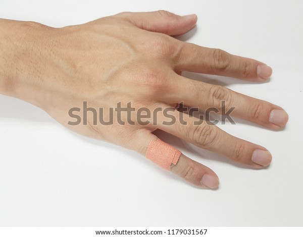 Close up of a hand that a finger has a band-aid on white background. Healthcare concept.