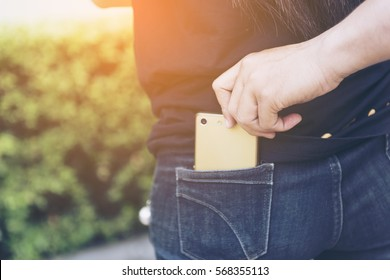 close up of a the hand of a thief stealing the phone to a woman