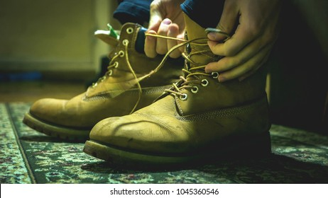 close up of hand tie shoelaces of warm boots