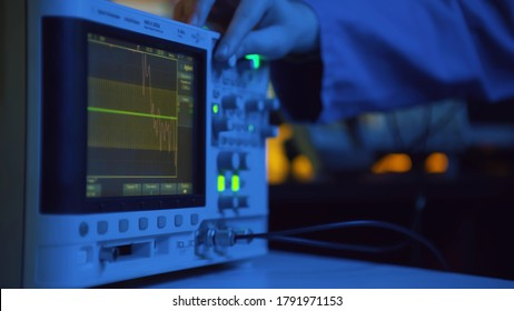 Close up of hand turning dial of modern electronic oscilloscope. Electronic engineer using EMI receiver during experiments or testing equipment in laboratory