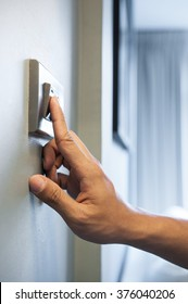 Close up of hand is turning on a light switch. Copy space.
