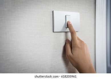 Close up hand turning on or off on grey light switch with texture background of interior wall at the house or hotel. Copy space.