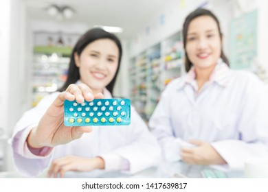 close up hand, two asian female pharmacist explain about how to use contraceptive drug, she holding contraceptive drug strip pack with her hand, Oral contraceptive pill