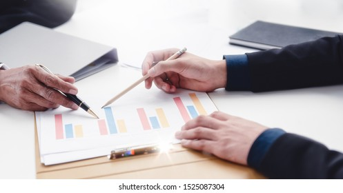 Close up the hand of two businessman discussing reporting the document on the desk in office room.