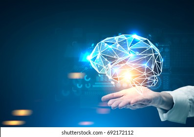 Close up of a hand of an unrecognizable businessman holding a glowing brain hologram. HUD and graphs in the background. Dark blue wall. Toned image mock up double exposure