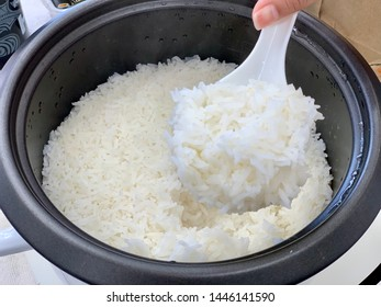 Close up with hand used to scoop rice from the rice cooker. - Shutterstock ID 1446141590