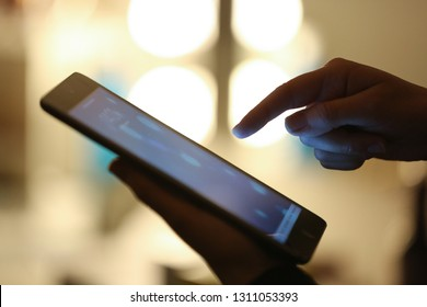 Close up of a hand using a smart phone or tablet at night.