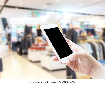 Close up hand using smartphone in a market or department store