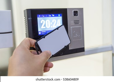 Close up  hand using white keycard to open door access control by digital access control lock and have digital clock on screen. Optional function with time attendance record.