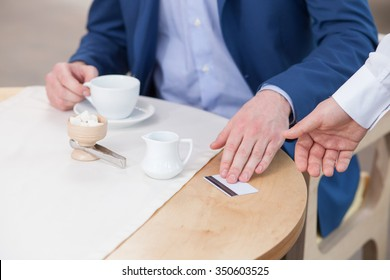 Close up of hand of waiter receiving payment for the order. The man is sitting at the table and giving him a credit card. He is drinking coffee