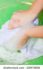Close up hand washing in plastic bowl