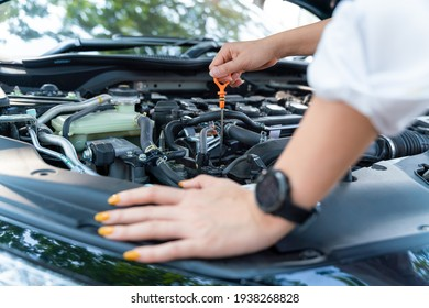 Close up hand of woman check the oil level in car engine.