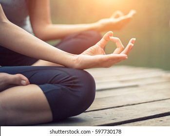 Close up hand. Woman do yoga outdoor. Woman exercising and zen relax and relaxation yoga at the nature background. Healthy and Lifestyle Concept