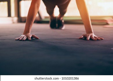 Close up hand of woman doing push ups in the gym. Light and silhouette.