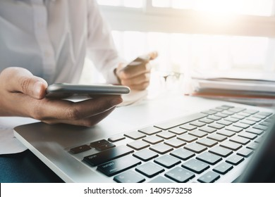 Close up hand of woman holding credit card and using laptop computer at home. Online shopping concept