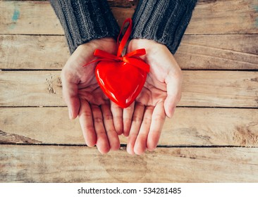 Close up hand woman holding and person red heart on wood table. Valentine background.